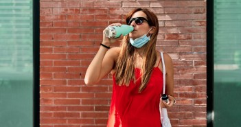 Young woman drinking water while wearing her mask. Concept of new normality and fight against the virus.
