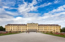 Wide-angle shot of schönbrunn palace in vienna, austria with a cloudy blue sky in the background