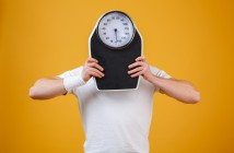 Young sports man hiding face behind weight scales