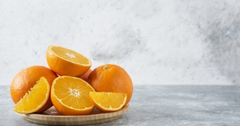 A wooden board full of juicy slices of orange fruit on stone background