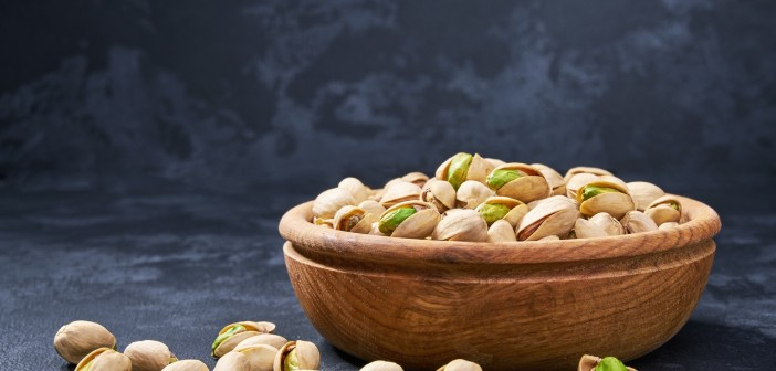 Pistachios in wooden bowl on black background, close-up.